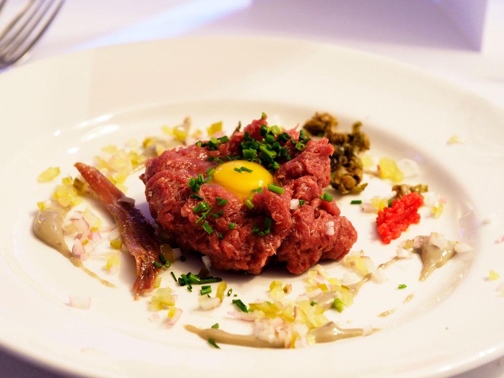 Tatar wołowy z przepiórczym jajkiem, pudrem z palonego dębu, prażonymi kaparami i emulsją z anchoi i chlorofilu
