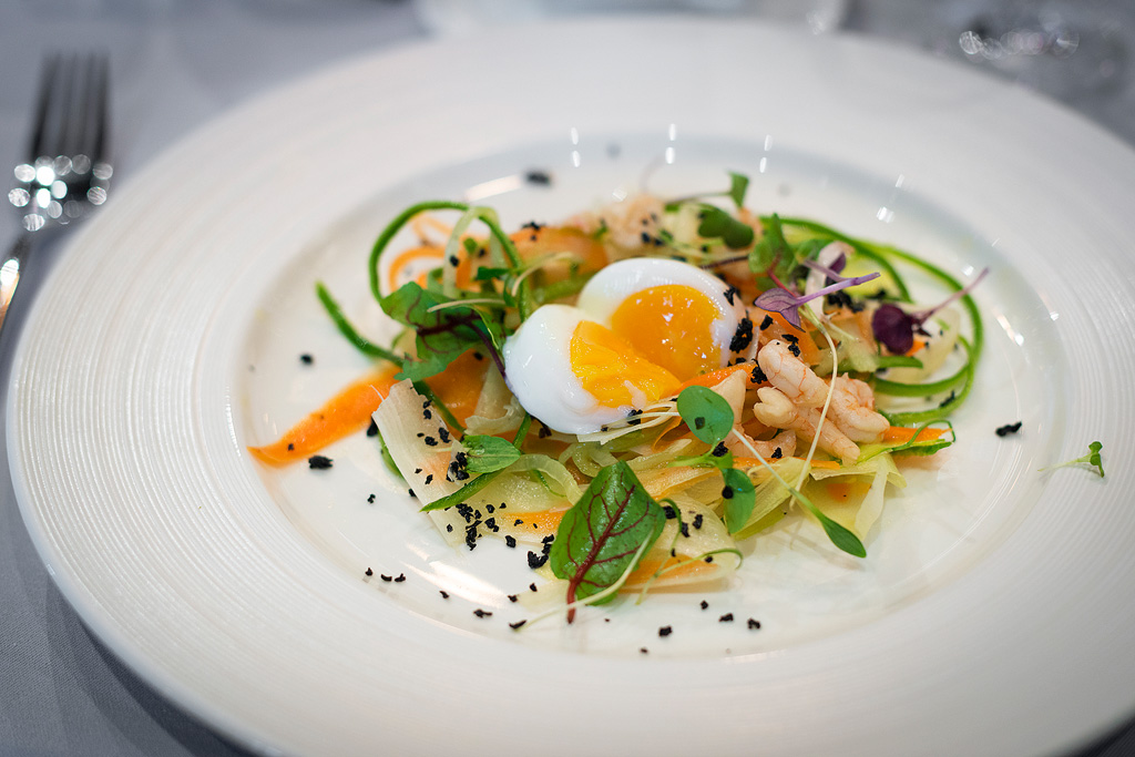 Jajko sous vide z krewetkami, sałatką wiosenną i pudrem z czarnych oliwek.